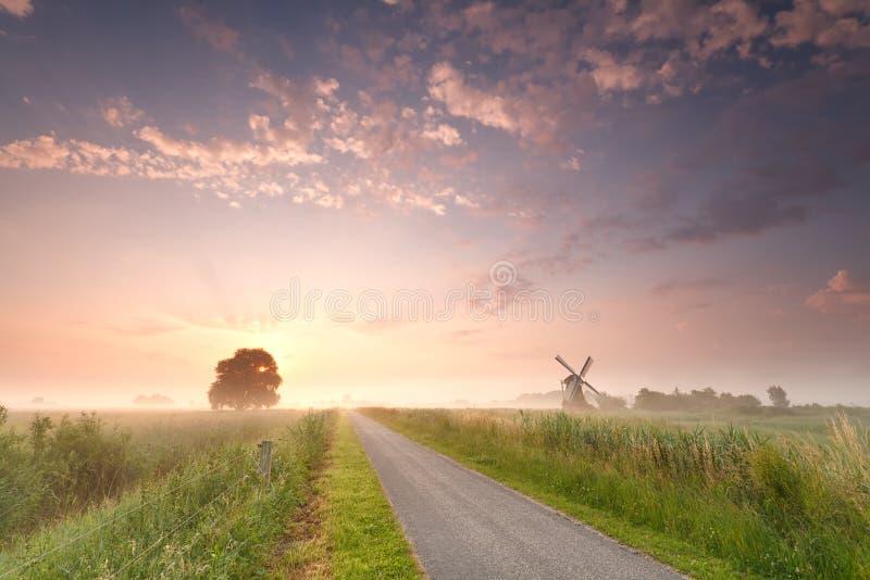 Härlig soluppgång på holländsk jordbruksmark med väderkvarnen fotografering för bildbyråer