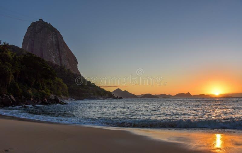 Härlig soluppgång på Praia Vermelha och det Sugarloaf berget arkivbilder