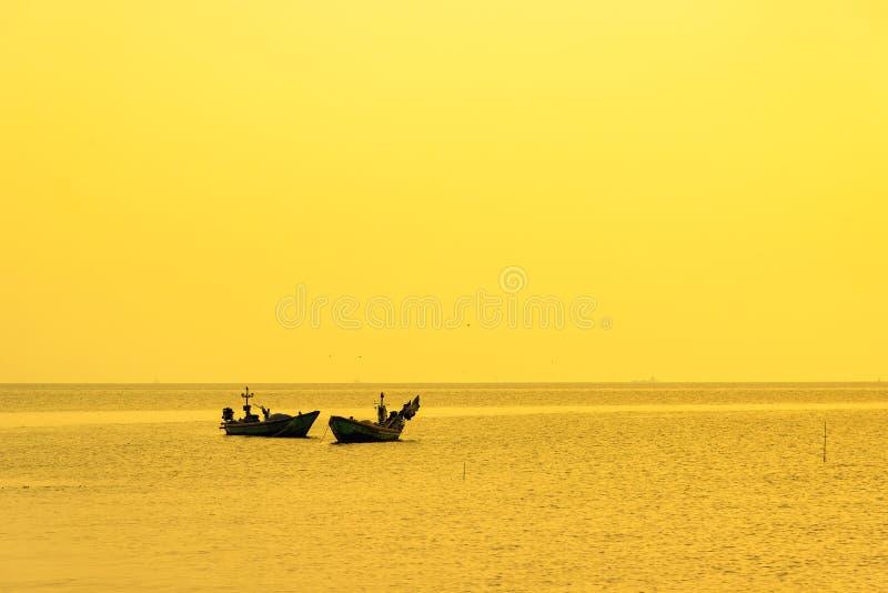 Härlig soluppgång på stranden och konturn av fiskebåten thailand royaltyfria bilder