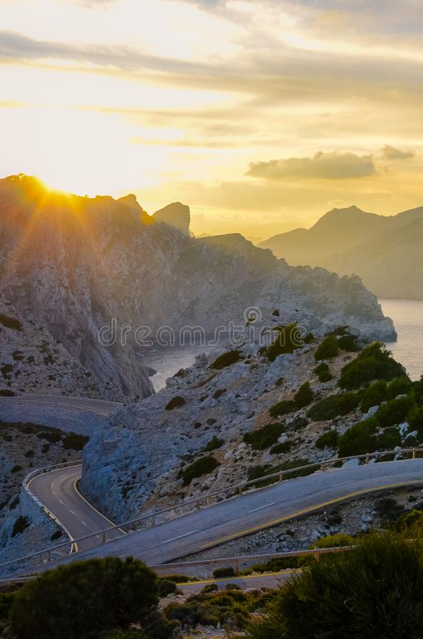 Härlig sommarsolnedgång i Lock de Formentor i spanska Mallorca Solen som går ner bak, vaggar och klippor orange sun _ royaltyfria bilder