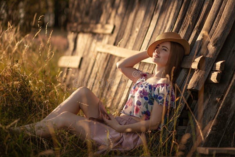 Härlig spenslig flicka med långt hår i en sugrörhatt som sitter nära ett trästaket och drömma Sommarafton p? solnedg?ngen F?r?lsk arkivbilder