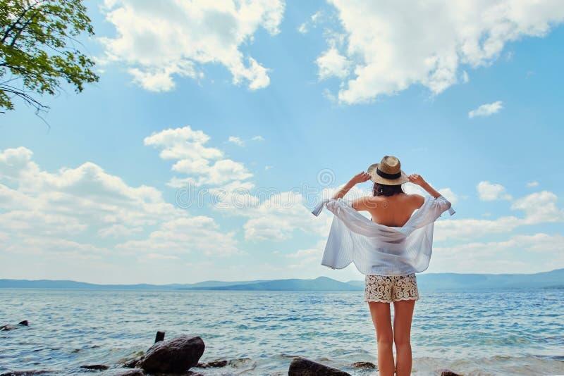 Härlig spenslig flicka som kopplar av på den steniga stranden av en stor la royaltyfria foton