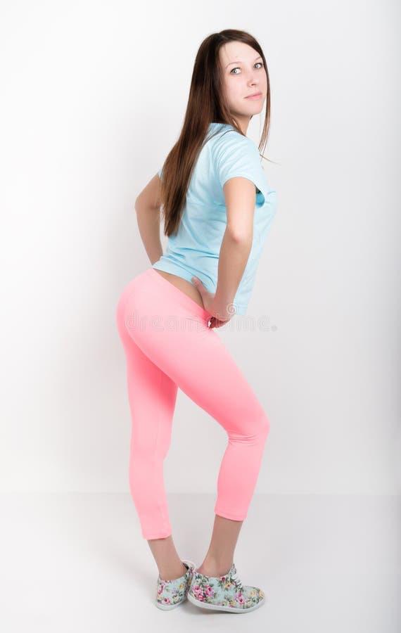 Härlig spenslig idrotts- flicka i rosa damasker, en blå ärmlös tröja och färgrika gymnastikskor royaltyfria foton