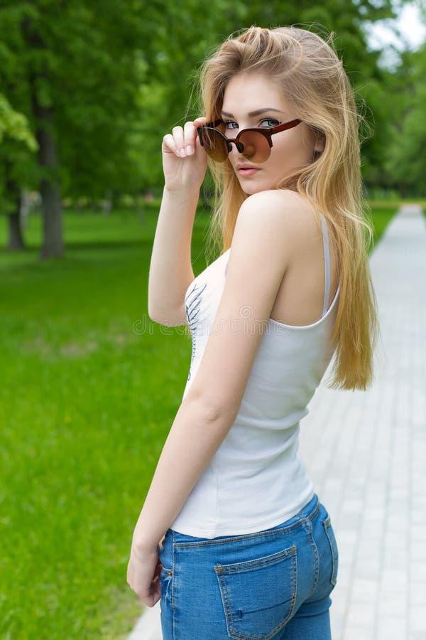 Härlig spenslig idrotts- ung sexig flicka i solglasögon i jeans- och gymnastikskogleet i parkerasommardagen royaltyfria bilder