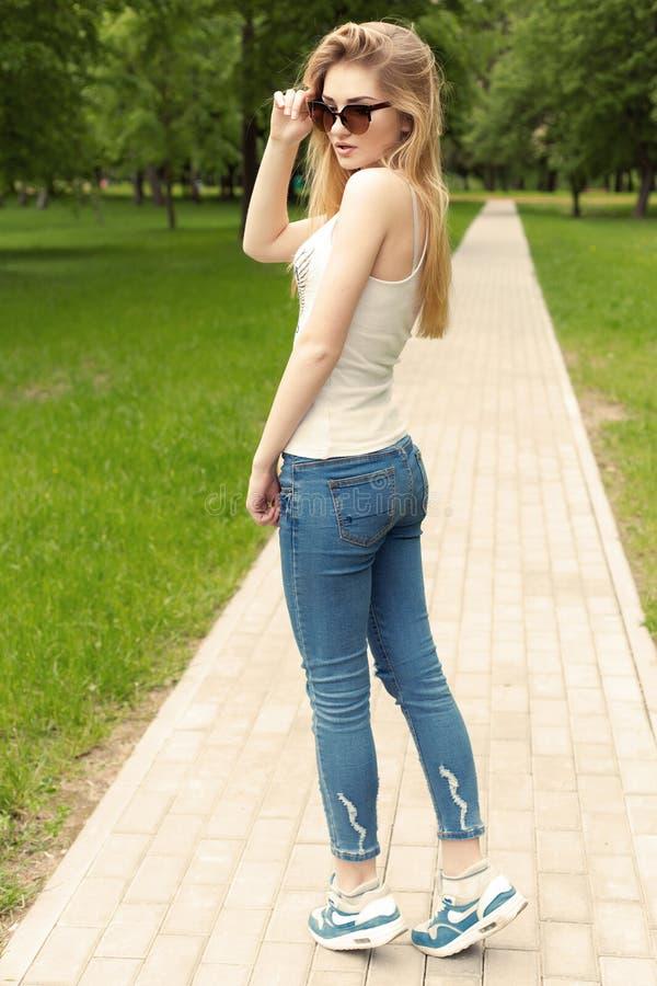 Härlig spenslig idrotts- ung sexig flicka i solglasögon i jeans- och gymnastikskogleet i parkerasommardagen fotografering för bildbyråer