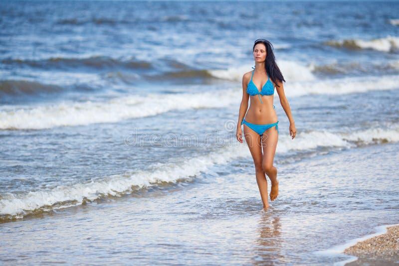 Härlig spenslig kvinna i en blå baddräkt som går på stranden arkivfoton