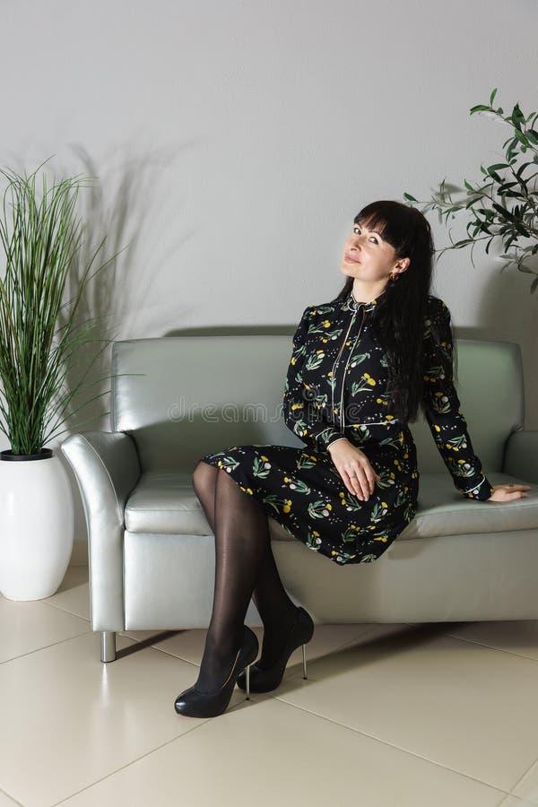 Härlig spenslig trettio-år-gammal kvinna som sitter på en silversoffa i rummet royaltyfri foto