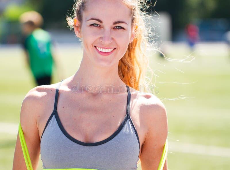 Härlig sportblondin kvinnan med ett hopprep på stadion S arkivfoto
