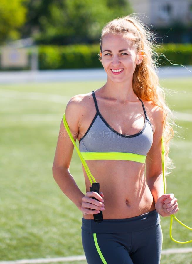 Härlig sportblondin kvinnan med ett hopprep på stadion S fotografering för bildbyråer