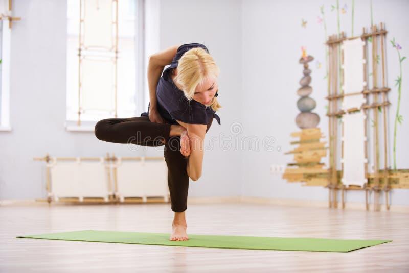 Härlig sportig asana för vridning för yoga för övningar för passformyogikvinna i konditionrummet royaltyfria bilder