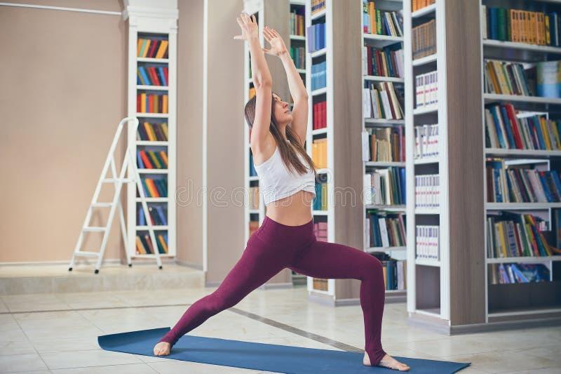 Härlig sportig färdig asana Virabhadrasana 1 för yoga för yoginikvinnaövningar - krigaren poserar 1 i arkivet royaltyfri fotografi