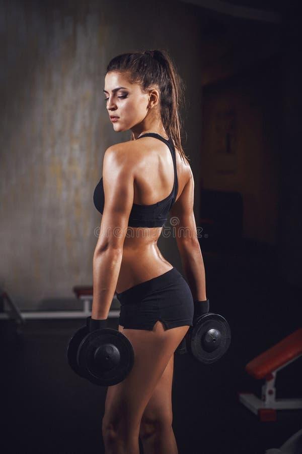 Härlig sportig muskulös kvinnagenomkörare i idrottshallen royaltyfri foto