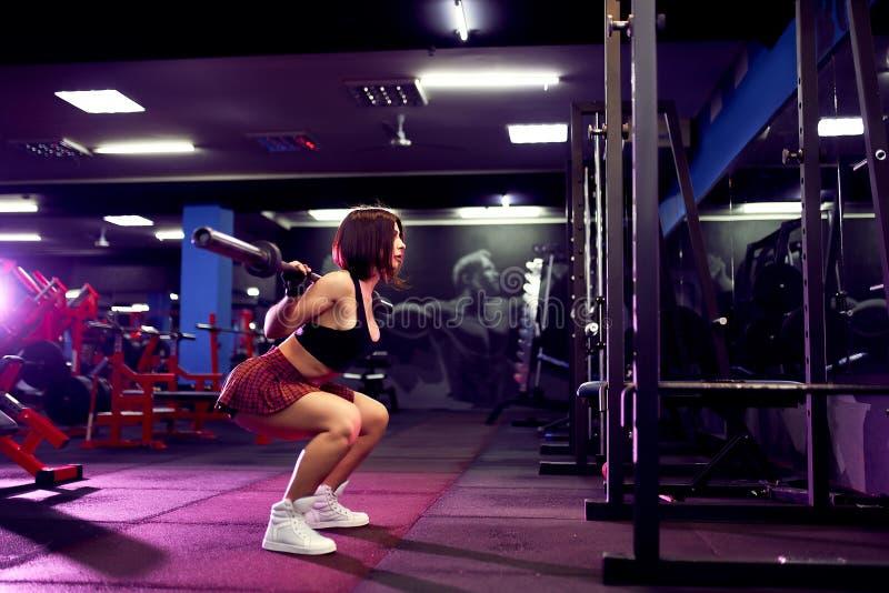 Härlig sportig sexig kvinna som gör satt genomkörare i idrottshall royaltyfri fotografi