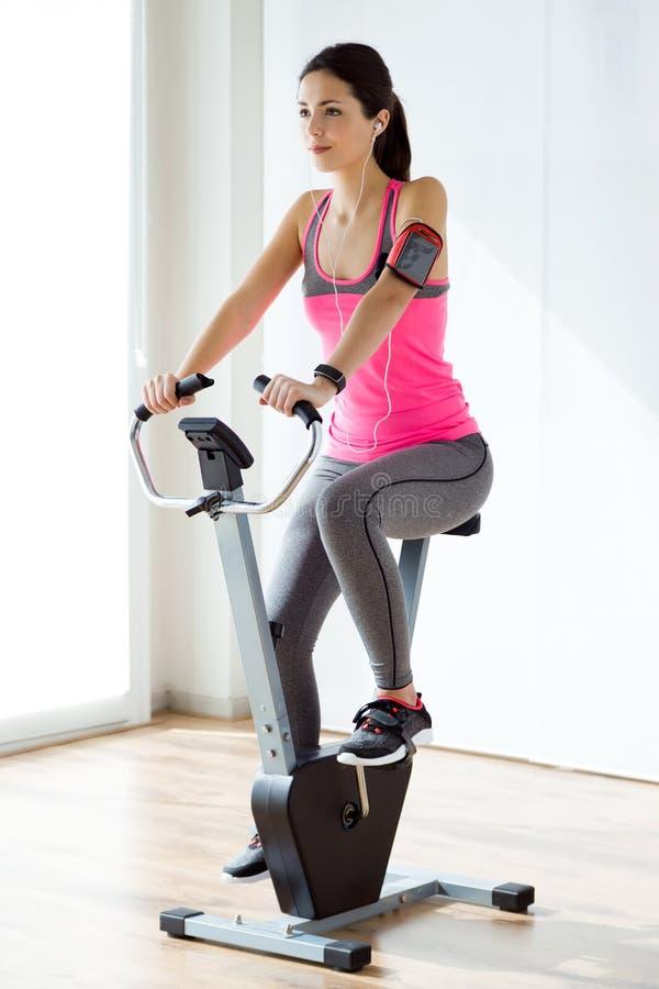 Härlig sportig ung kvinna som gör övning i idrottshall royaltyfri bild