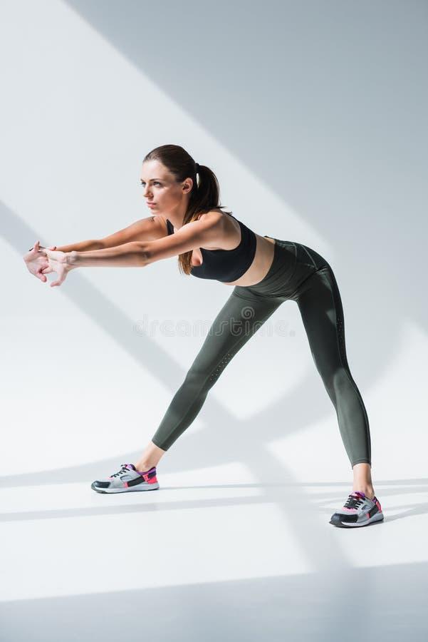 härlig sportig ung kvinna som sträcker för genomkörare arkivfoton