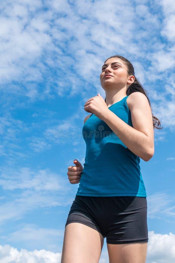 Härlig sportive flickaspring längs den härliga sandiga stranden, hea arkivfoto