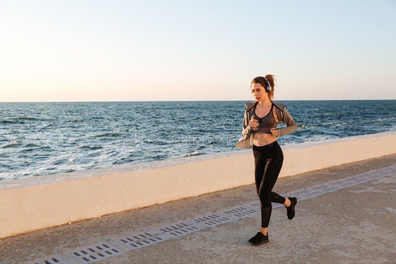 Härlig sportive kvinna i hörlurar som kör på sjösidan arkivbilder