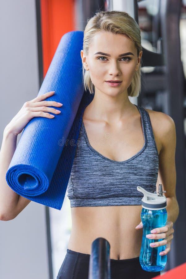 härlig sportive kvinna med rullande yoga som är matt på skuldra och flaskan av att se för vatten fotografering för bildbyråer