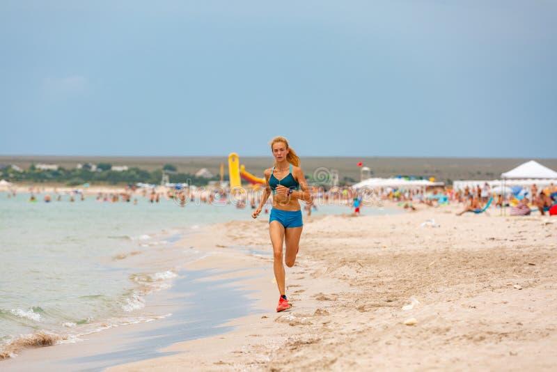 Härlig sportive kvinnaspring längs den härliga sandiga stranden, sund livsstil som nära tycker om aktiv sommarsemester royaltyfri foto