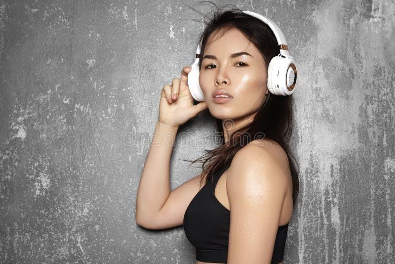 Härlig sportkvinna med stor vit hörlurar Modell som lyssnar musiken Konditionstående, perfekta kroppformer royaltyfri fotografi