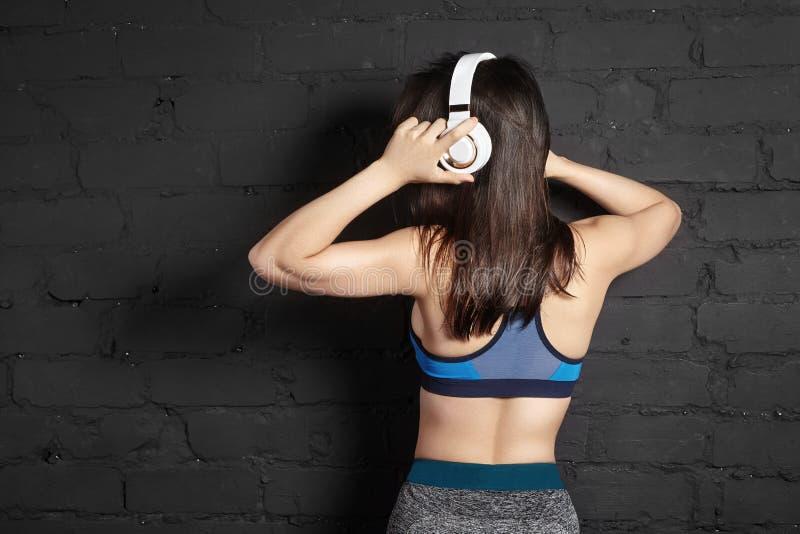 Härlig sportkvinna med stor vit hörlurar Modell som lyssnar musiken Konditionstående, perfekta kroppformer arkivbild