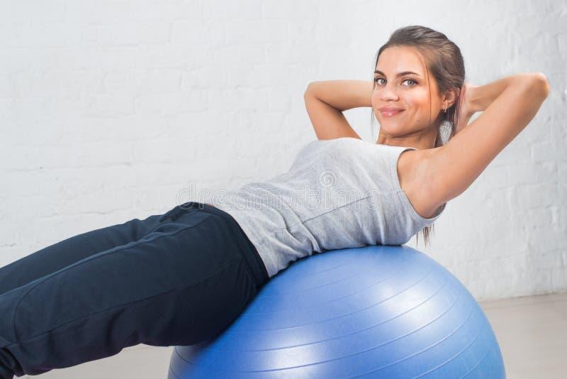Härlig sportkvinna som gör konditionövningen som sträcker på boll Pilates sportar, hälsa arkivbilder