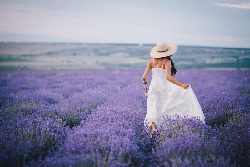 Härlig spring för ung kvinna i ett lavendelfält royaltyfri bild