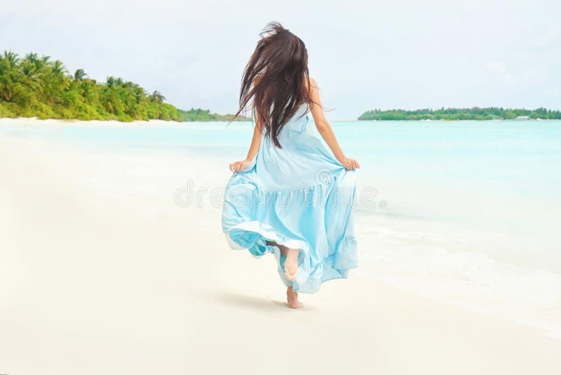 Härlig spring för ung kvinna längs havsstranden royaltyfria foton