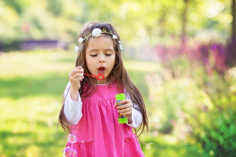 Härlig stående av den söta älskvärda lilla flickan som blåser tvålbubb arkivbilder