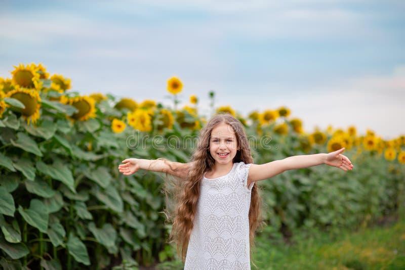 Härlig stående av en flicka med långt hår på en bakgrund av ett fält med solrosor royaltyfri fotografi