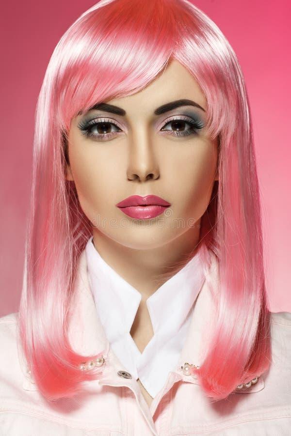 Härlig stående av en flicka med rosa hår på en rosa bakgrund fotografering för bildbyråer