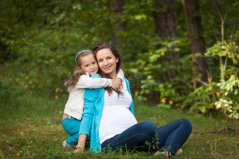 Härlig stående av gravida kvinnan i skogen arkivfoto