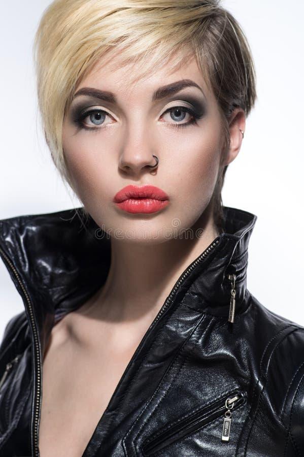 Härlig stående av kvinnan med den kort frisyren och piercing arkivfoto