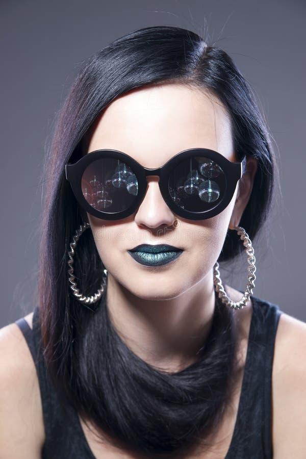 Härlig stående för kvinnamodemodell i solglasögon med blåa kanter och örhängen Idérik frisyr och smink arkivbilder