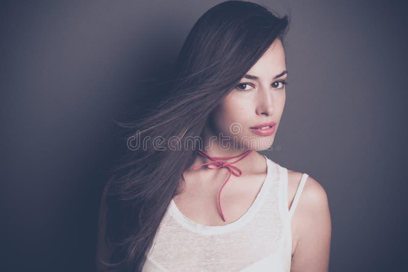 Härlig stående för ung kvinna för mörkt hår i den vita t-skjorta studien royaltyfri bild