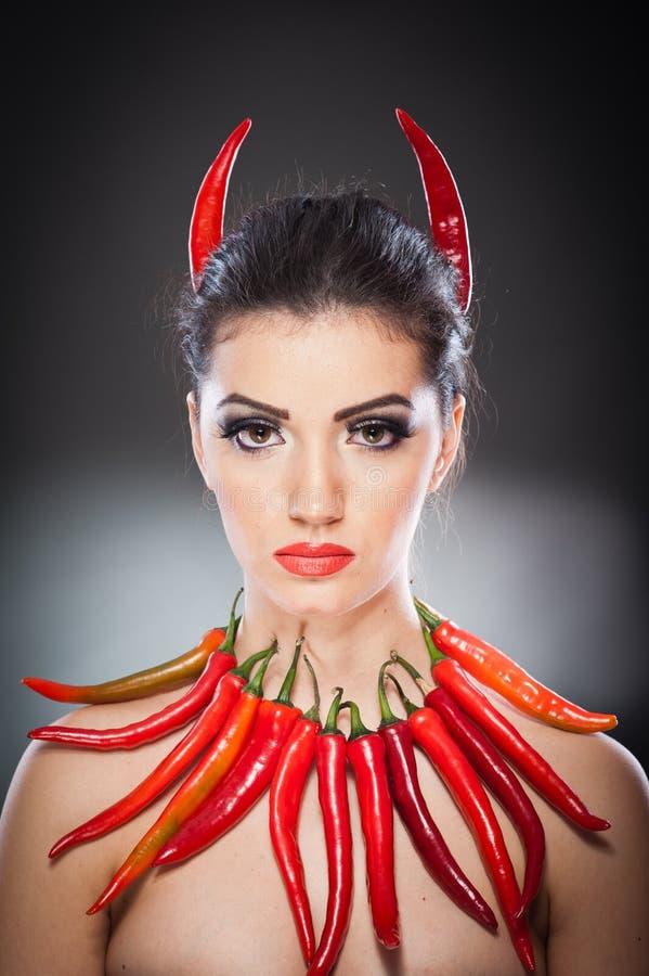 Härlig stående för ung kvinna med glödheta och kryddiga peppar, modemodell med idérikt matgrönsaksmink royaltyfri bild