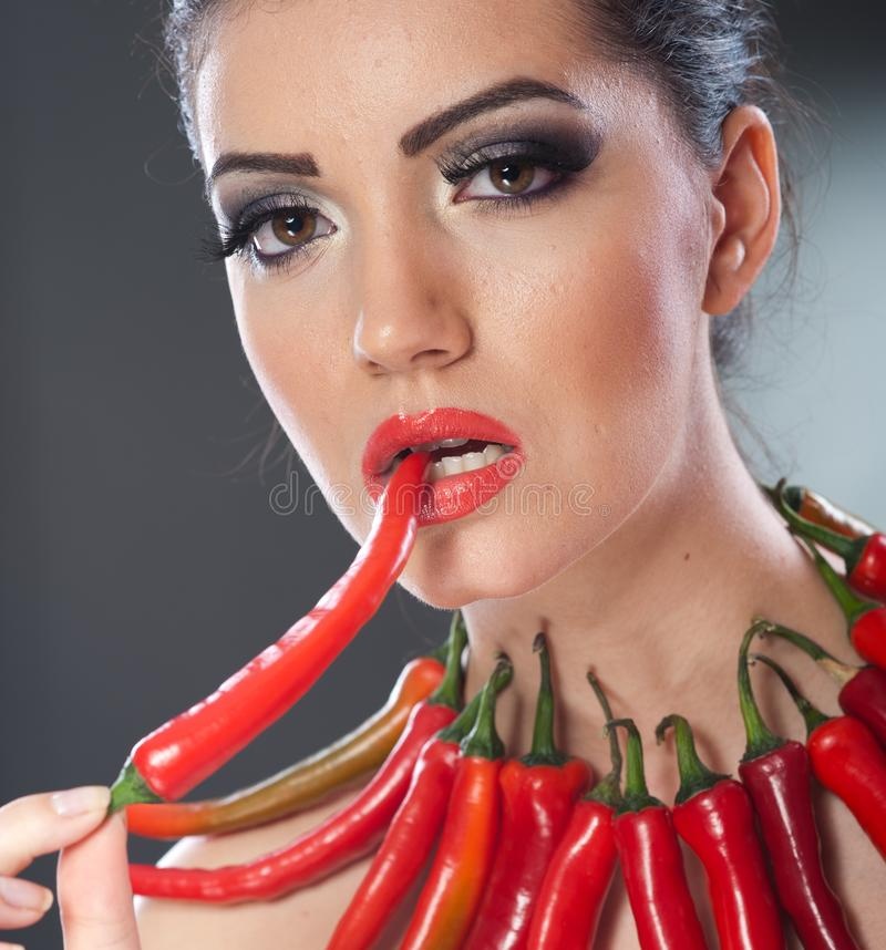 Härlig stående för ung kvinna med glödheta och kryddiga peppar, modemodell med idérikt matgrönsaksmink arkivbild
