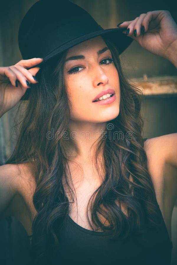 Härlig stående för ung kvinna med hattsommardag i staden arkivfoton