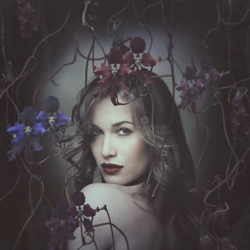 Härlig stående för ung kvinna som omges av orkidér royaltyfri fotografi
