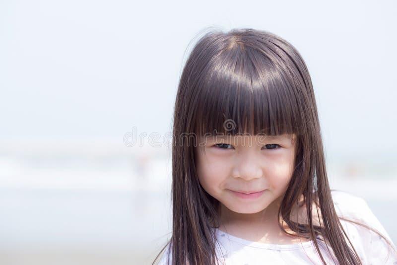 Härlig ståendeliten flickaasiat av le stå på stranden arkivfoto