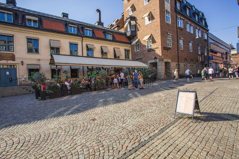 Härlig stadsgatasikt Gå peple och folk som sitter i utomhus- restaurang royaltyfria foton