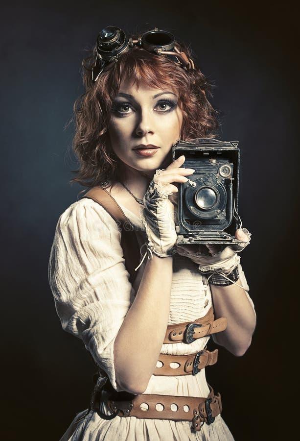 Härlig steampunkflicka med den gamla kameran royaltyfri fotografi