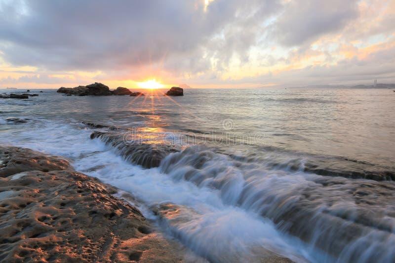 Härlig stenig strand som är upplyst vid de guld- strålarna av morgonsolljus på den Yehliu kusten, Taipei, Taiwan fotografering för bildbyråer