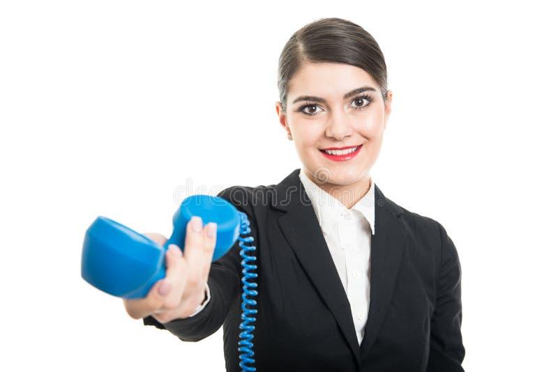 Härlig stewardess som räcker den stora blåa telefonmottagaren fotografering för bildbyråer