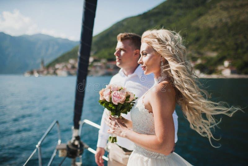Härlig stilfull brud i en vit bröllopsklänning på den lyxiga yachten royaltyfria foton