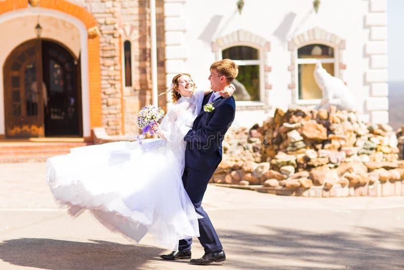 Härlig stilfull brudgum som rymmer den sagolika lyckliga emotionella bruden och har utomhus- gyckel royaltyfri foto