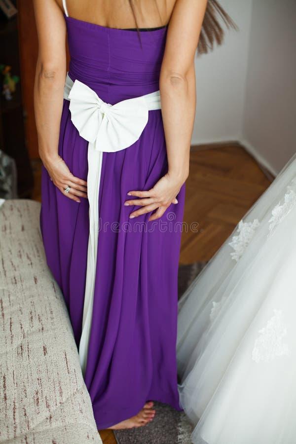 Härlig stilfull brudtärna i en violett klänningportionbrud in royaltyfri bild