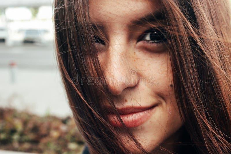 Härlig stilfull brunettflicka som ler med fräknar på backgro arkivfoto