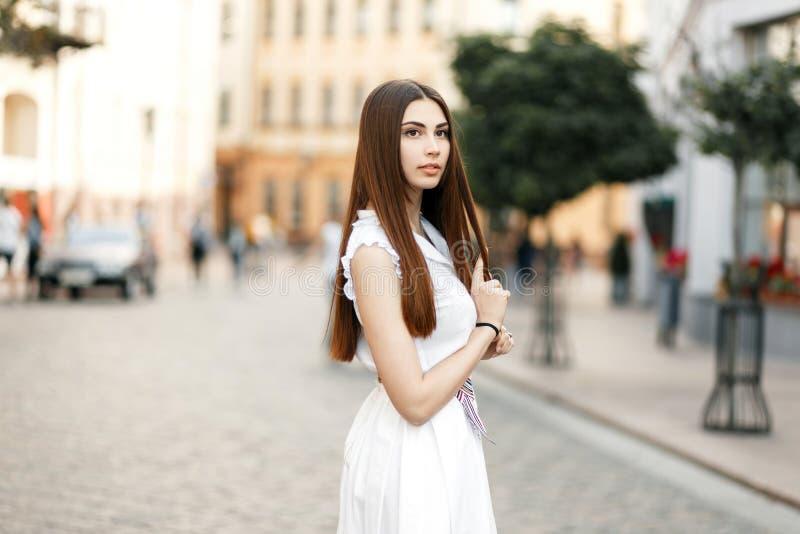 Härlig stilfull elegant brunettflicka i en vit klänning för mode arkivbilder
