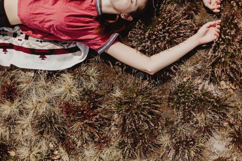 Härlig stilfull kvinnahipster som ligger i gräs och kopplar av i s fotografering för bildbyråer